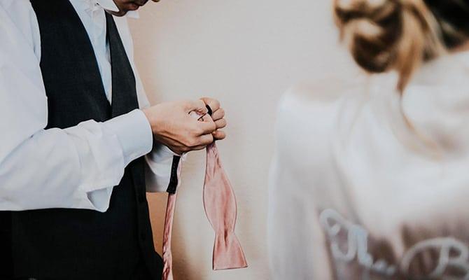 Groom holding silk bowtie