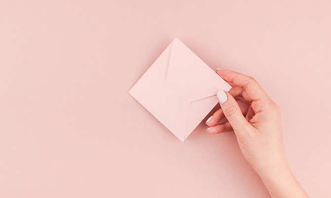Woman holding a cute pink invite for Galentine's Day