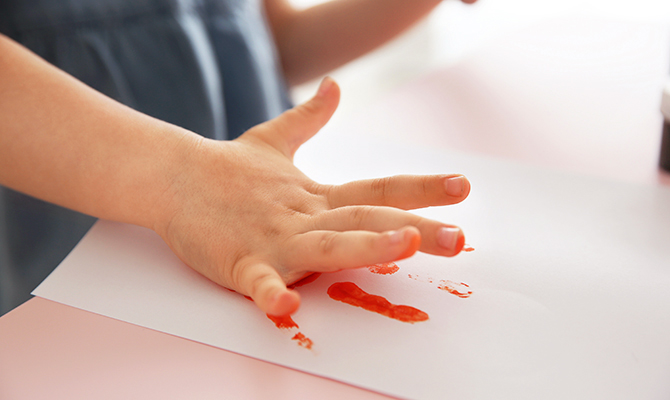 Child making hand print on paper