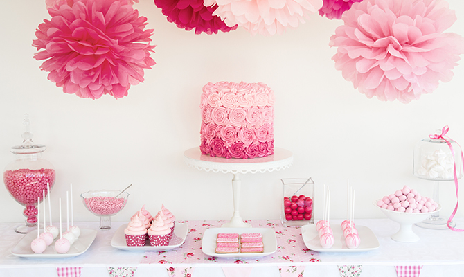 Table filled with fun pink decorations for a Galentine's Day party