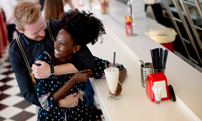 Couple hugging by the bar in the diner