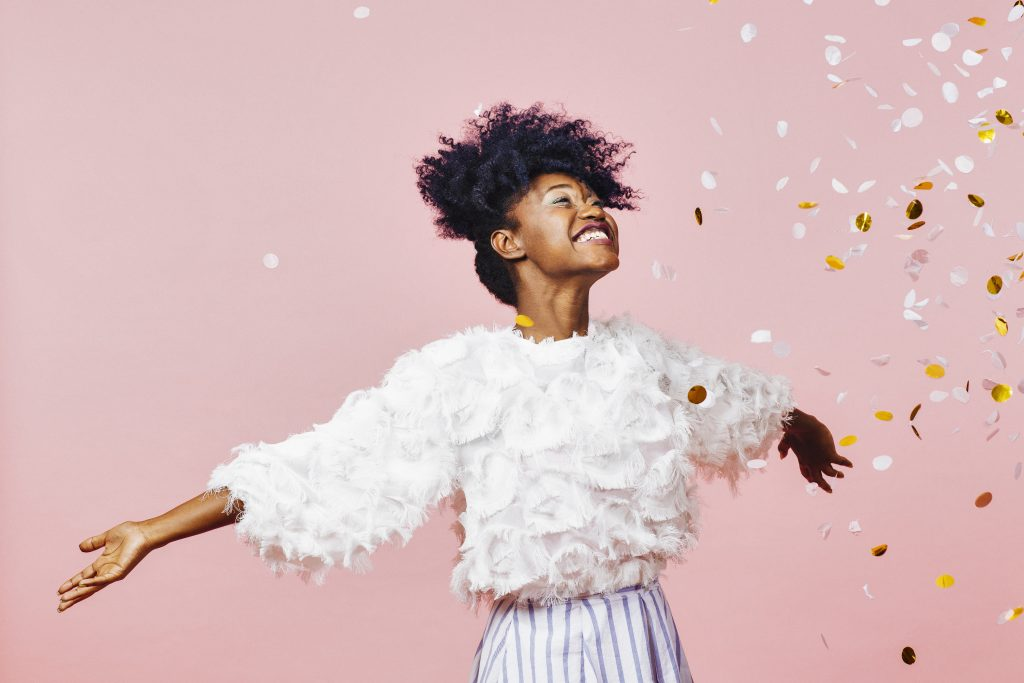 Happy woman with confetti on pink background