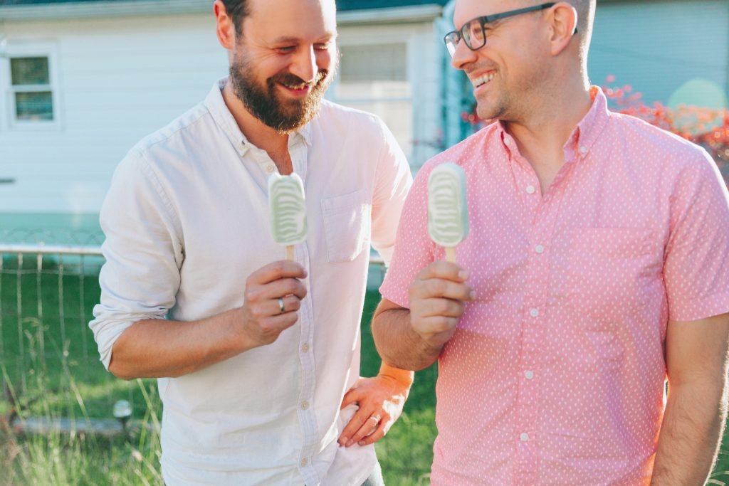 Two men eating ice cream and laughing together.