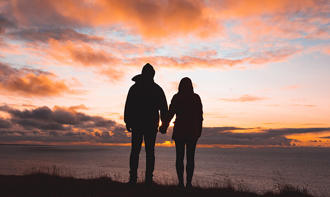 Couple standing in front of sunset